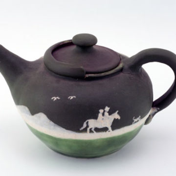 Walter B. Stephen, Westward Ho Teapot, 1943, glazed and porcelain decorated stoneware, 4 ⅜ × 9 × 6 ½ inches. Gift of Andrew Glasgow, 2010.26.03.82.