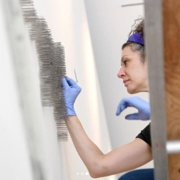 @citizentimes Shannon Sberna, an art handler and member of the installation team at the Asheville Art Museum, pushes individual pins into the wall as she works to install artist Maya Lin's Pin River-French Broad in the atrium of the new museum on July 17, 2019. The series of thousands of pins follows the map of the French Broad River from end to end. The piece will be completed at a member's event at the museum on July 26. Staff at the Asheville Art Museum are hoping to announce a day for the reopening soon. (? by staff photographer @angeliwright ).