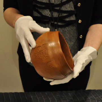 A curator handles a work of art